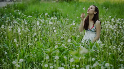 stock-footage-young-woman-blowing-dandelion-and-laughing-on-a-summer-field