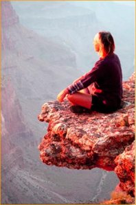 woman-meditating-on-cliff-extension-jutting-out
